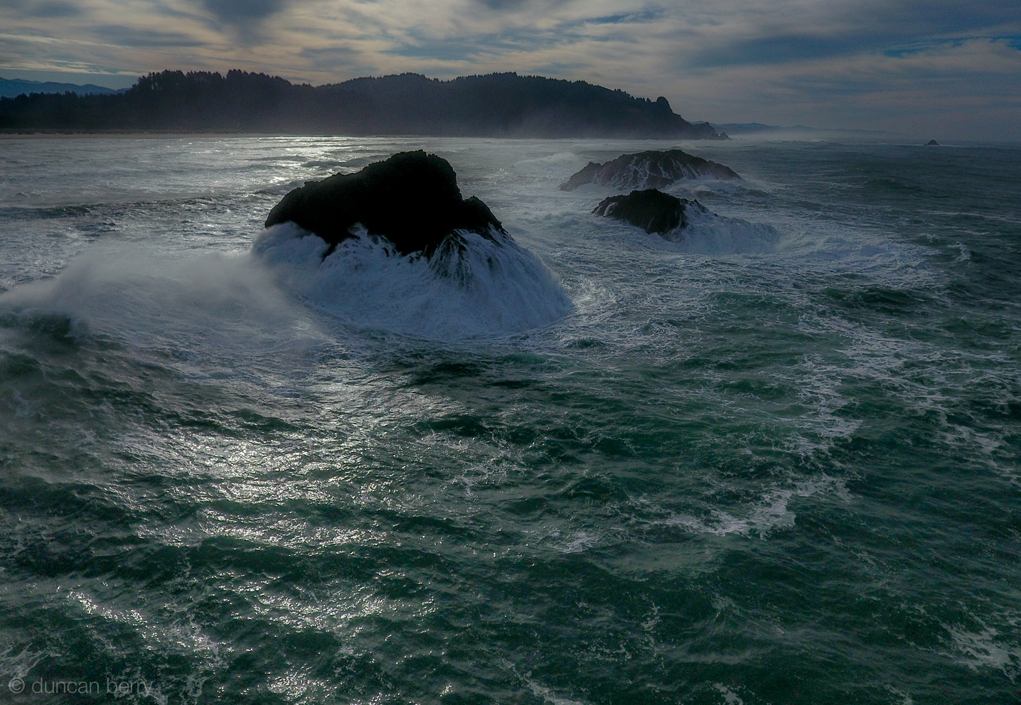Three rocks with huges waves crashing